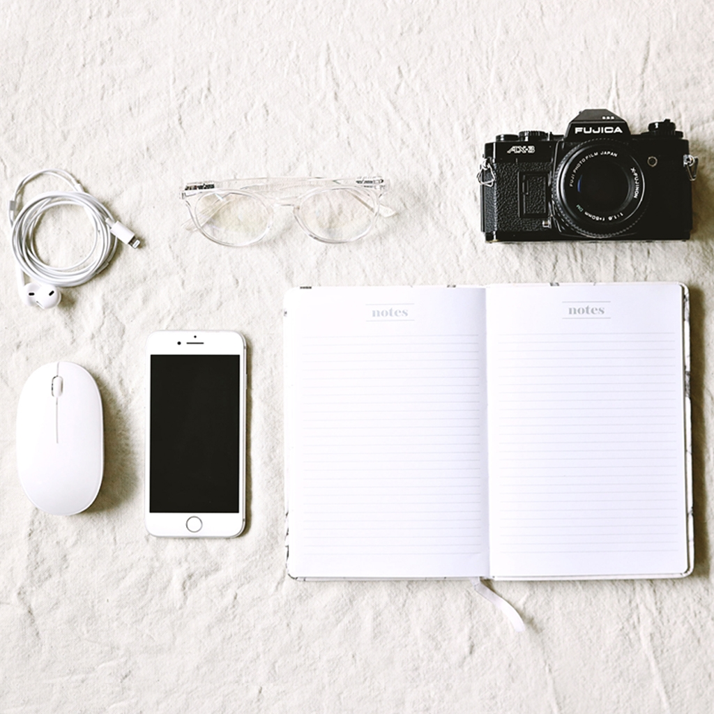 Photo of camera, notebook, phone, glasses, phone cable, and mouse