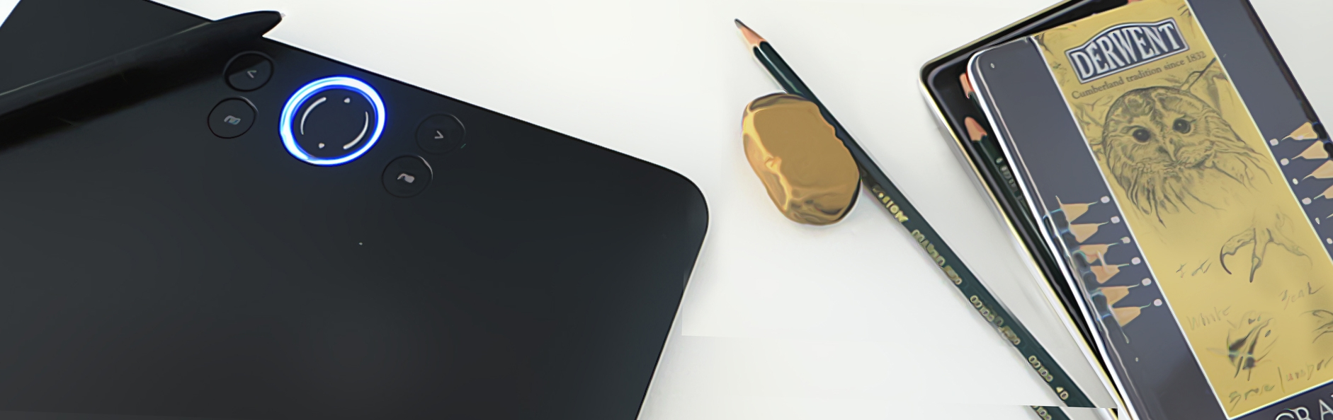 computer pen, tablet, pencil, eraser, and sketching pencils in a tin container photograph